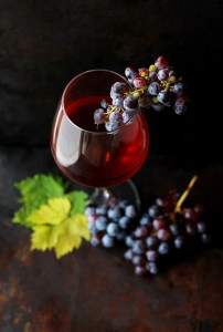 A glass of red wine is shown with grapes sitting on the brim. Red wine is one of Sardinians secrets to longevity.