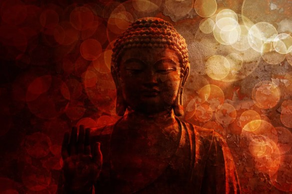 A bronze Zen Buddha statue is shown with a raised palm on a blurred textured red background. This image represents the Buddha's teachings on the 3 marks of existence.