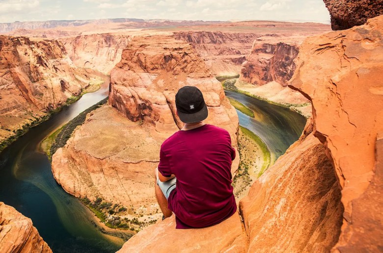 A man sits on the ledge of the grand canyon looking out in awe at the river below. This picture represent the idea of stepping outside of the comfort zone.