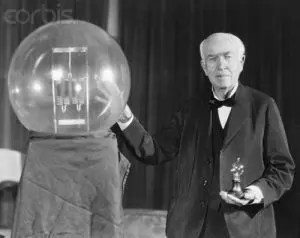 A picture of Thomas Edison is shown as he stands next to a giant light bulb. He is one of history's most notable famous failures.