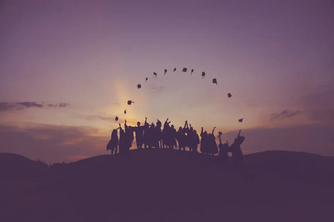 A graduating class is pictured throwing their caps into the air making a perfect arch. This picture represents the idea of Mudita, or finding joy in the joy of others.