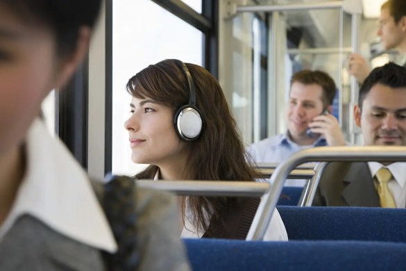 A commuter on a train is shown with headphones on and a slight smile on her face as she looks out the window. The Audible App for iOS and Android gives you the opportunity to turn down time into time for personal growth.