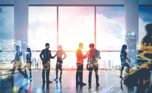 A business meeting is shown with individuals standing and a city skyline superimposed on the picture. It represents the idea that social capital can transform entire communities.