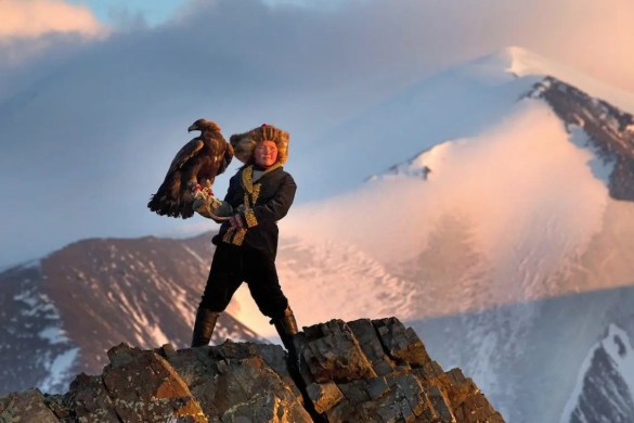 A picture is shown of Aisholpan standing high on a mountain top holding an eagle. She is a 13-year-old girl who is the subject of The Eagle Huntress, one of our films selected for our list of inspirational documentaries.
