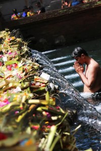 A spiritual seeker is shown bathing in a holy Hindu river with his hands in prayer position.