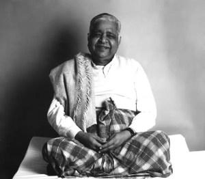 A picture of legendary Vipassana teacher S.N. Goenka is shown sitting in a meditation position.
