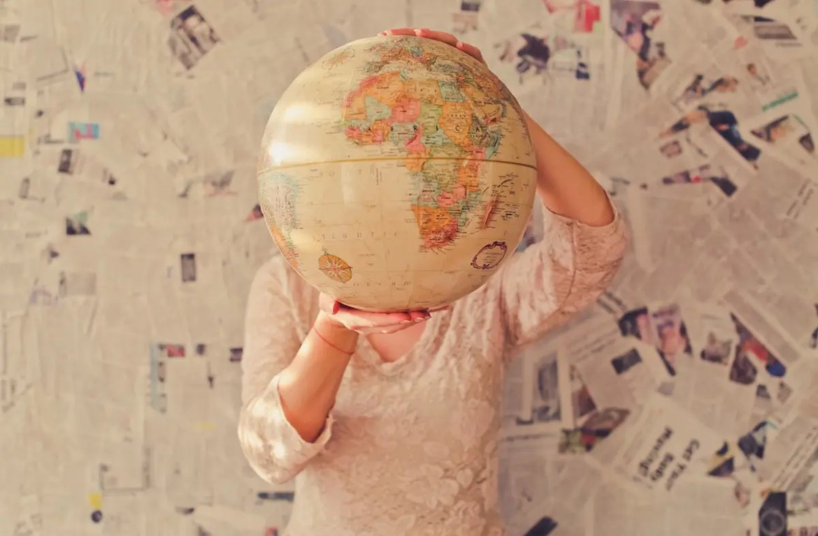 A picture of a woman is shown who is holding a globe in front of her face. This image represents the idea that we must focus our attention on helping the greater good.