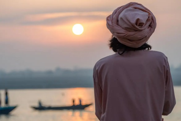 An image is shown of a Hindu seeker looking out over the Ganges as the sun begins to set. This image serves as the featured image for Balanced Achievement's article about Brahman and Atman.