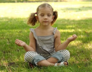 An image shows a little girl meditating in a park.