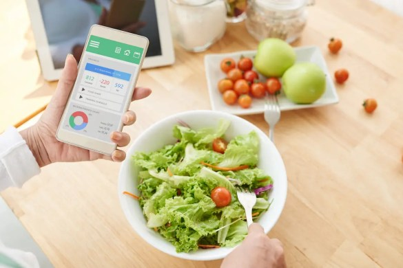 A woman is shown checking nutrition information and calories on her phone when eating a salad and fruit. This picture serves as the featured image of Balanced Achievement's iThrive article that looks at the Eat Right Now App.