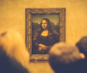 An image is shown from the museum which houses the Mona Lisa. While the famous painting is in the background, onlookers are closer to the camera and you can see the back of their heads.