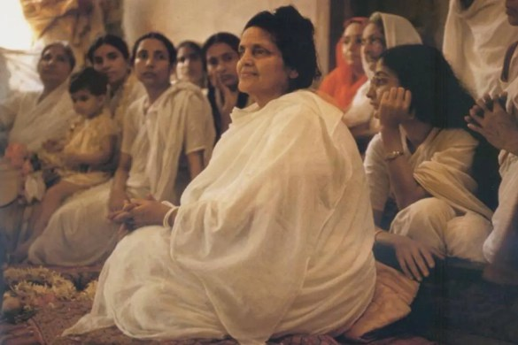 A picture of the great Hindu saint Anandamayi Mi is shown as she sits in a meditative position on the floor with a crowd of people around her.