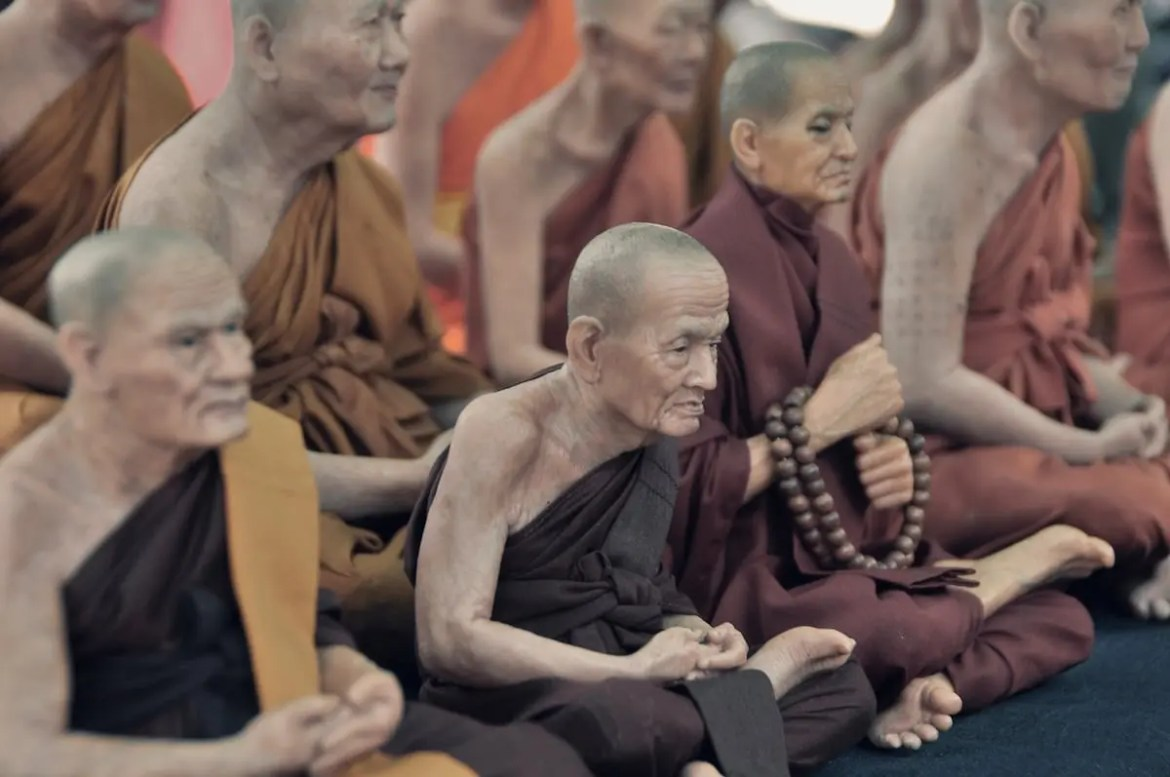 An image shows a group of Buddhist monks sitting in a traditional meditation posture. This picture serves as the featured image of Balanced Achievement's meditating with mindfulness and concentration article.