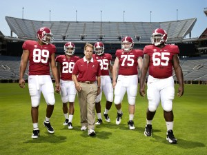 The University of Alabama football coach Nick Saban is shown walking with 5 of his players.
