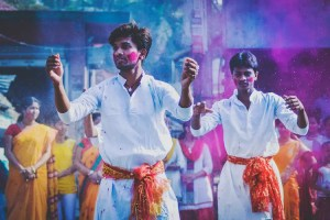 An image shows 2 young Hindu men dancing in part of the yearly Holi rituals.