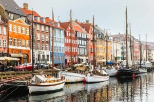 An image is shown of a Scandinavian pier with boats and colorful buildings.