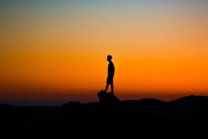 The silhouette of a man is shown as he stands on a raised rock with a beautiful orange sky behind him.