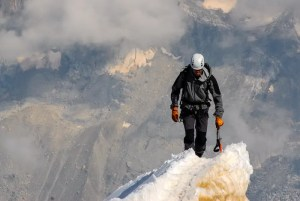 An image of a mountain climber is shown as he reaches an extremely high ice summit.