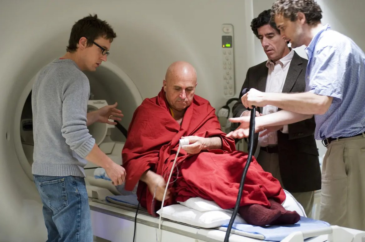 Richard Davidson is shown with 2 assistants conducting research on celebrated Buddhist monk Matthieu Richard. This picture serves as the featured image for Balanced Achievement's article examining the benefits of meditation.