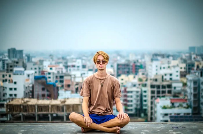 A young wise man is shown sitting on the rooftop of a building in a meditative posture. This image represents creativity as being one of the many benefits of meditation.