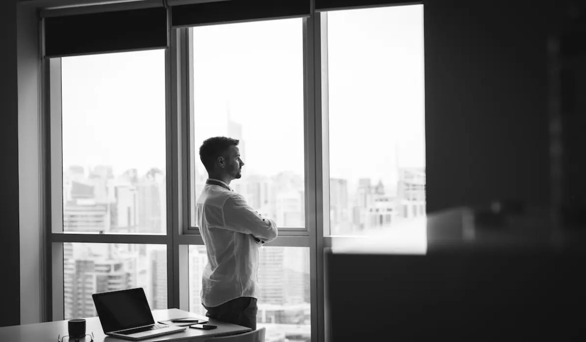 A young CEO is pictured looking out of the window in his office and pondering his next business move. This picture serves as the featured image for Balanced Achievement's article on becoming the CEO of yourself.
