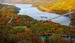 An image shows an aerial view of a river with a boat on it. The surrounding land is covered in tress that are showing fall colored leafs. This image represents the idea of impermanence which is a major aspect of the idea that we need to make today memorable.