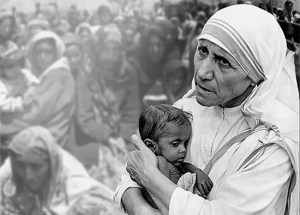 An image shows a picture of Mother Teresa compassionately holding a baby as a crowd of poverty stricken onlookers watches in awe. Mother Teresa's actions are a prominent example of moral elevation.