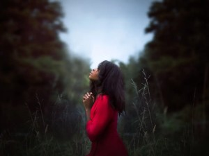 A young woman is shown praying gratefully in a field.