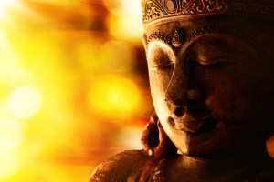 An image shows a bronze Buddha statue with gold and yellow lights in the background. This image represents the idea that the Buddha's psychological-based teachings can help move us towards higher levels of subjective well-being.