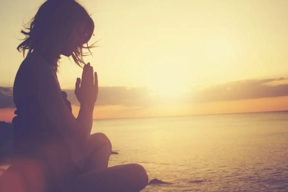 An image shows a young woman practicing yoga on the beach as the sun shines down on her. This picture serves as the featured image for Balanced Achievement's article on the Silent Witness.