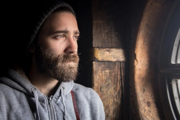 An image shows a young man with a beard contently looking out a window as if he is deep in thought. This picture serves as the featured image of Balanced Achievement's article on core beliefs.