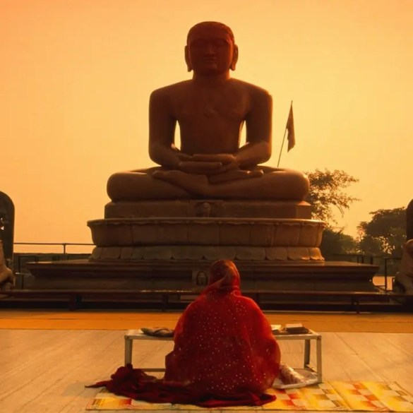 An image shows the back of a meditator sitting by herself as she looks upon a giant statue of a individual in a meditation posture. This picture serves as the featured image of Balanced Achievement's article that focuses on 20 meditation quotes.