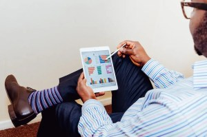 An image shows a fancy dressed business man looking at a fancy tablet device with numbers and graphs on it. This image represents the idea that how we perceive our success is one of our most important core beliefs.