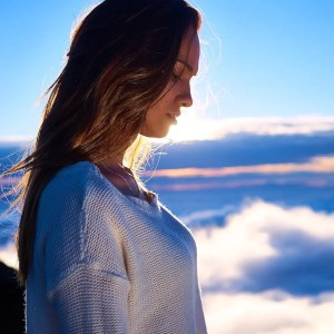 An image shows a woman whose in the mountains near the clouds as the sun shines down on her in an illuminating way. This image represents the idea that cultivating wisdom is essential to win the game of real life.