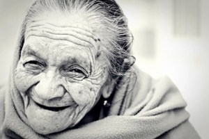 A black and white image shows an older lady smiling happily. This picture represents the idea that the ultimate aim needed to win the game of real life is to be happy.