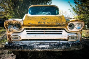 An image shows an old beat up Chevy that is completely broken down.