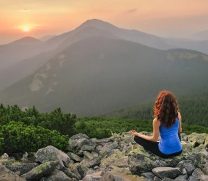 An image shows a woman high in the mountains meditating as the sun sets over a number of mountains peaks in the foreground. This image represents the idea that we can practice meditation for success to help us achieve our goals.
