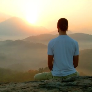 An image shows a young man high in the mountains as the sun shines down on him. This image represents the idea that it's possible to practice meditation for success and reach the summit of achievement.
