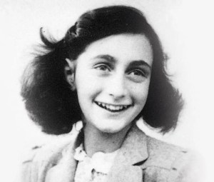An black and white picture shows a young Anne Frank smiling from ear to ear.