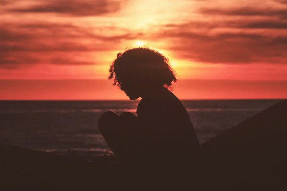 An image shows the silhouette of a woman sitting by herself thinking with the sun setting in the background. This picture serves as the featured image for Balanced Achievement's articles on cognitive schemas & subjective well-being.