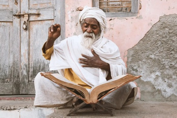 A picture is shown of an old Indian sadhu (saint) sitting and reading sacred texts near a Hindu temple. This picture serves as the featured image for Balanced Achievement's article titled Hinduism's Eternal Wisdom: Karma and Dharma.