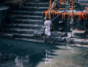 An image shows an untouchable working on the Ghats in Varanasi. This image is featured in Balanced Achievement's article on karma and dharma.