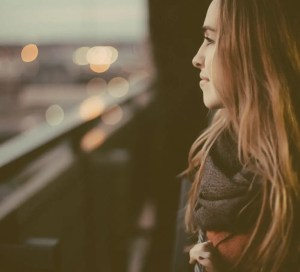 An image shows a young woman as she smiles while looking out of over the edge of a bridge. This image brings to life the idea that our schemas have a major impact on our subjective well-being.