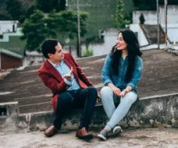 An image shows a young couple sitting on a sidewalk curb engaging in a lively and fun conversation. This image represents the idea that we can promote positive change in others by approaching our relationships with empathy.