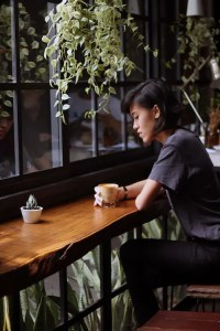 An image shows a young lady sitting by herself in a coffee shop as she looks down at her table in deep thought. This image illuminates how we use cognitive schemas to make sense of the world.