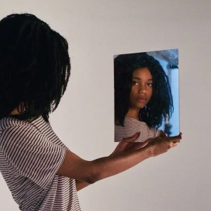 An image shows a young woman holding up a mirror as she looks into it. This image represents the idea that we all have self-schemas which expose the ways in which we think about ourselves.