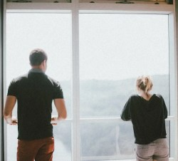 An image shows a young couple looking outside of a balcony window as they stand far apart from one another. This image represents the idea that all too many of us communicate unconsciously and unproductively.