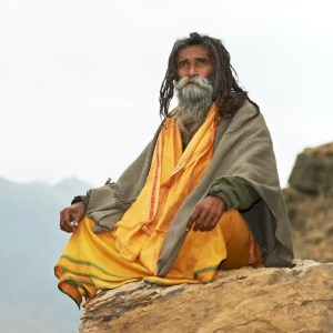 An image shows Indian an old Hindu sadhu in traditional saffron colored clothing as he sits in a meditation posture. This image is featured in Balanced Achievement's article on Quotes from the Upanishads.