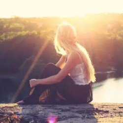 An image shows a woman sitting on the cliff of a bluff as the sun sets over a river and forest. This image represents the idea that we can enrich our lives by asking ourselves conscious questions.