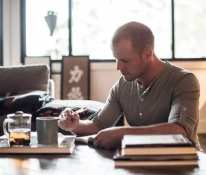 An image show the legendary self-help leader Tim Ferriss writing at a table with a cup of tea.
